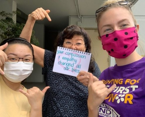 """Partners with kupuna holding written sign saying """"your compassion & empathy changed all our lives"""""""